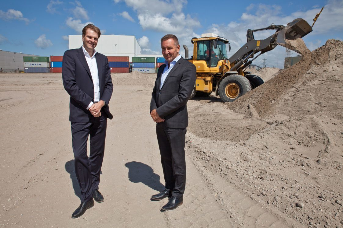 Cuno Vat (l) en Ron Neele naast de vestiging op de Maasvlakte, de plek waar de nieuwe loods voor de opslag van gevaarlijke goederen moet verrijzen.